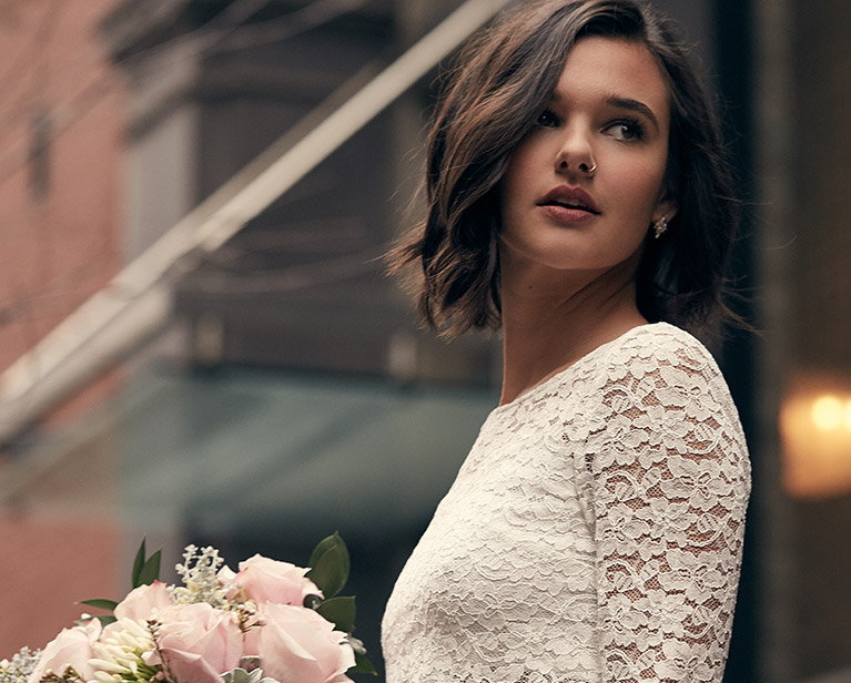Bride in long sleeve lace wedding dress looking back over her shoulder in city background