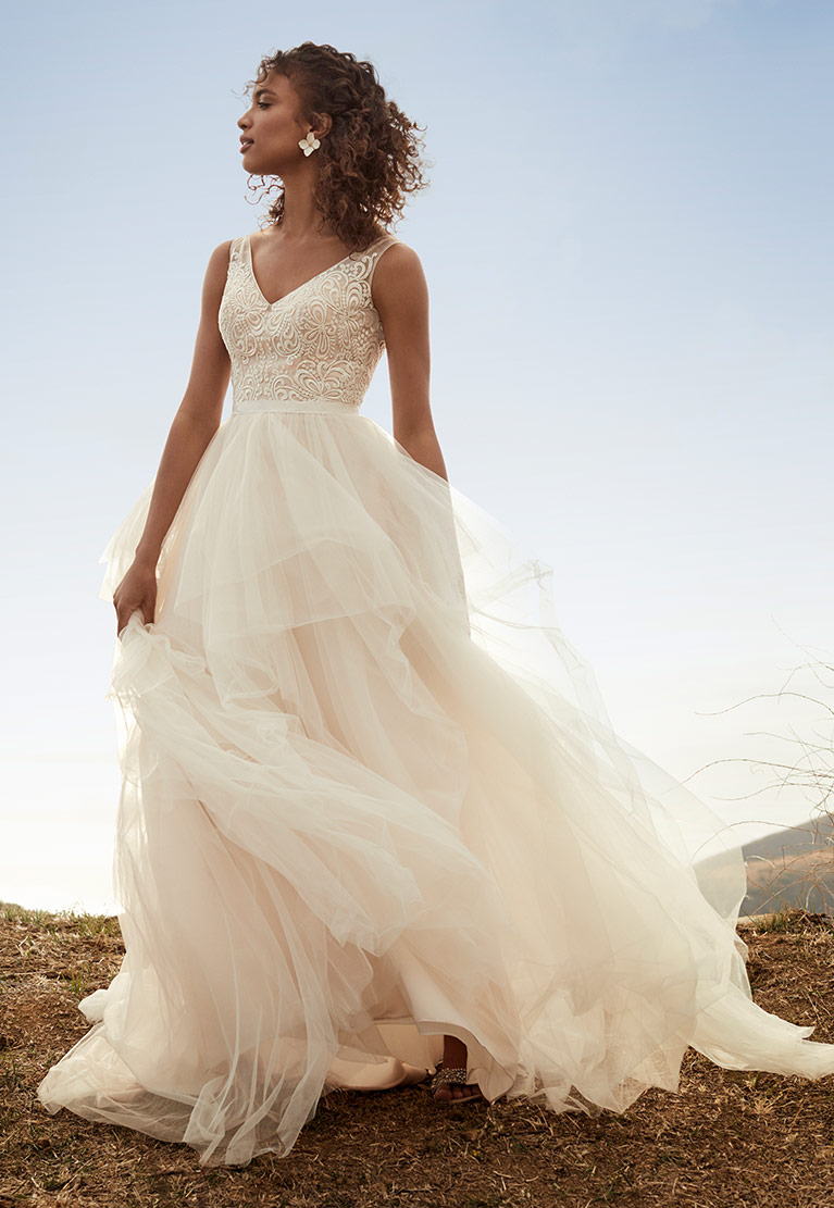 Bride in wedding dress standing on a hill