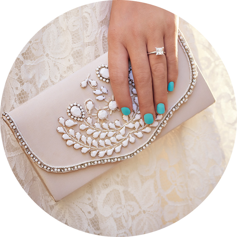 Close up of bride with teal nails holding beaded clutch