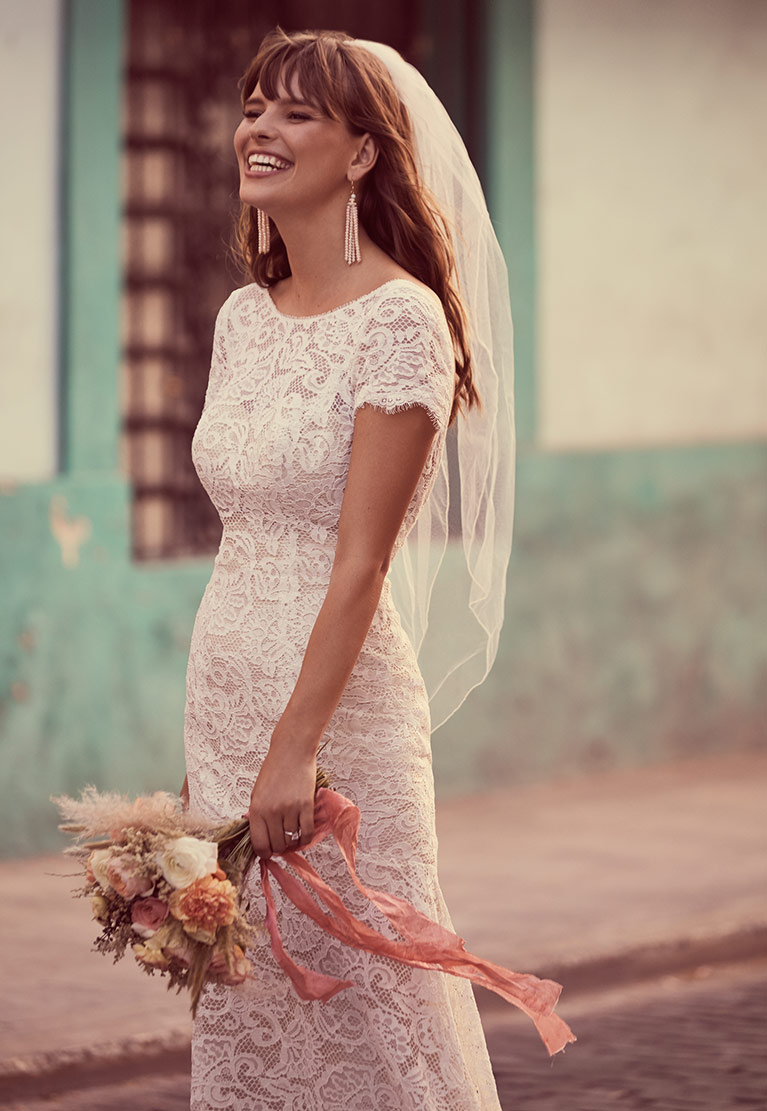 Bride smiling with veil and bouquet walking down the street