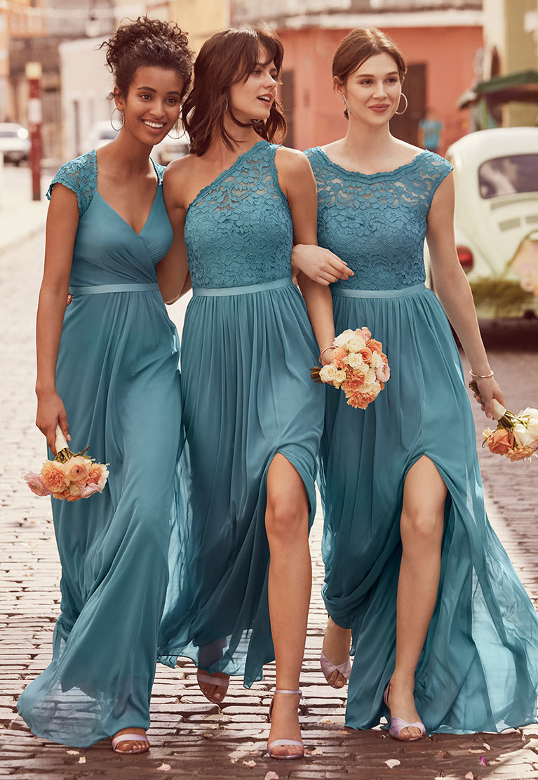Bridesmaids walking down street in blue lace dresses