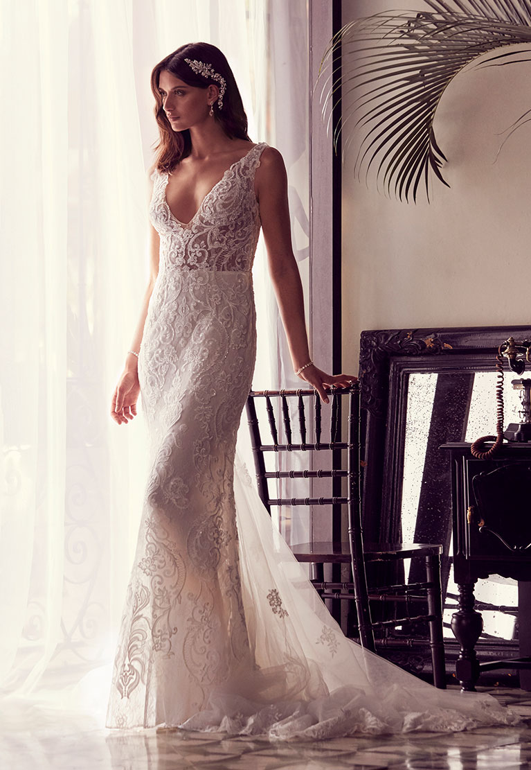 Bride in alluring wedding dress standing against chair