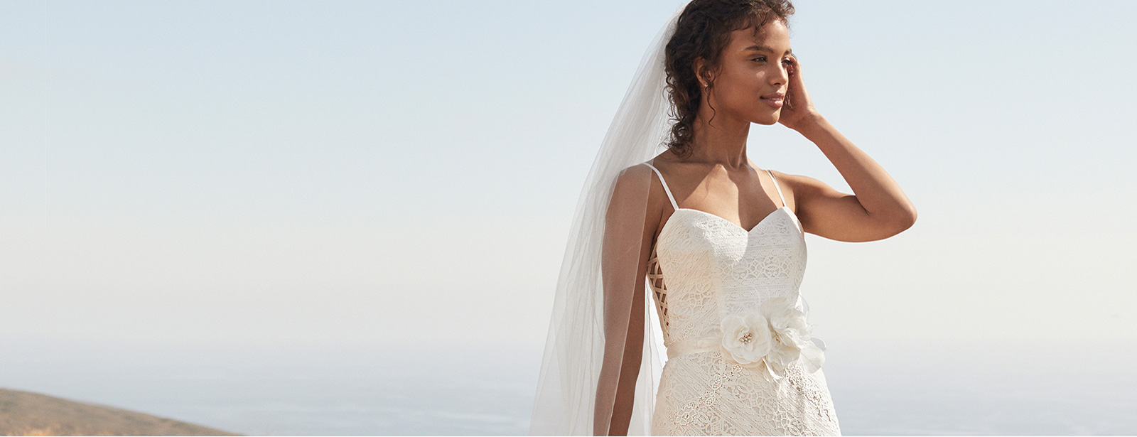 Bride on beach in Galina lace spaghetti strap gown with side cut-outs and floral sash