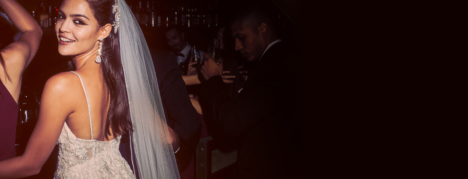 Back shot of bride turning to camera wearing an embellished spaghetti strap gown, statement earrings and long veil