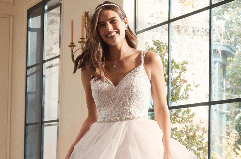 Smiling bride in front of window wearing beaded bodice gown with full skirt