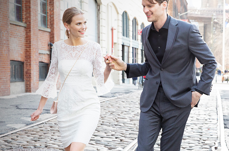 Bride wearing lace LWD with bell sleeves, holding hands with groom while walking on cobblestones
