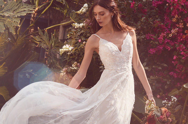 Bride in a garden wearing lace V-neck gown with flowing skirt
