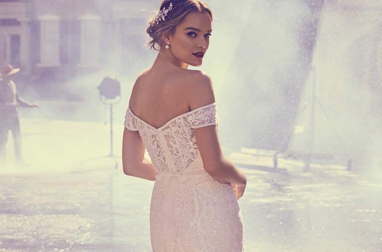 Bride wearing off the shoulder lace Oleg Cassini gown on movie set