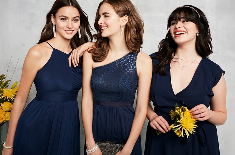 Bridesmaids wearing Reverie mix and match navy dresses, one holding a sparkling handbag and one carrying yellow flowers