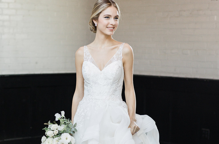 Seated bride wearing strapless bridal gown with dramatic skirt