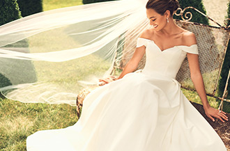 bride wearing off the shoulder davids bridal collection wedding gown.