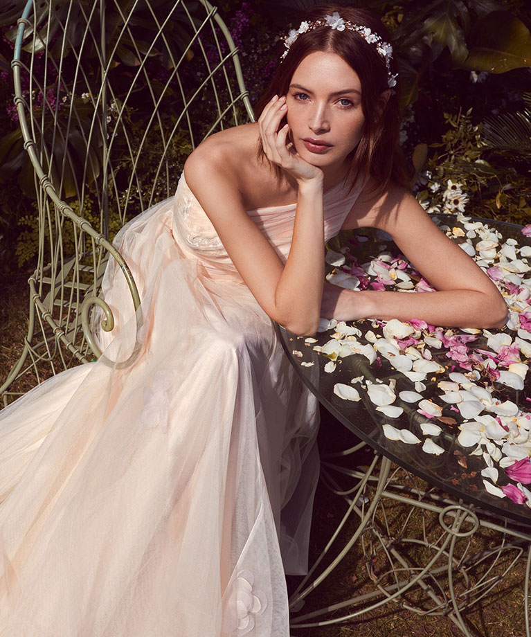 e409c4f439bdc Bride seated at an outdoor garden table with rose petals ...