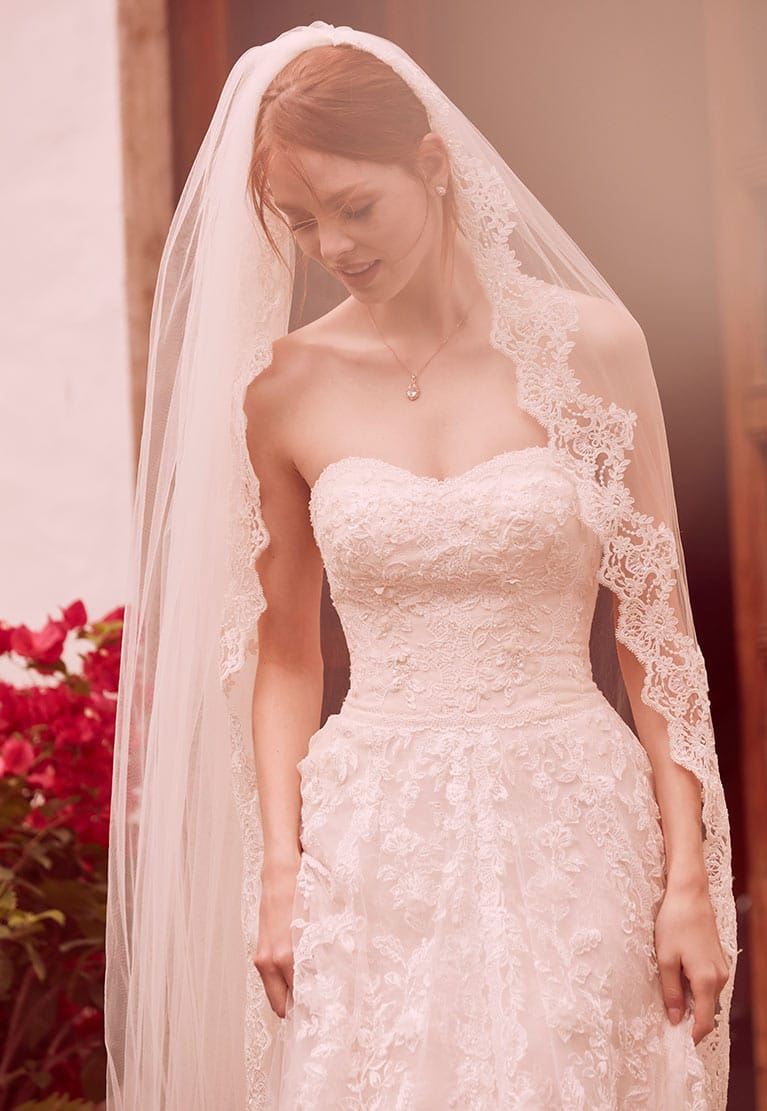 Bride with veil in strapless wedding dress gazing at ground