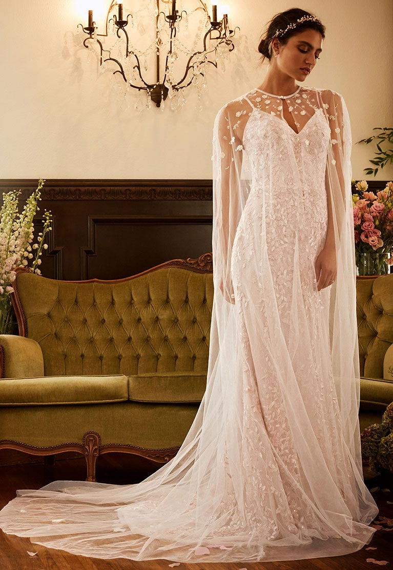 Melissa Sweet Wedding Dresses Bride Standing By Elegant Couch Wearing Capelet