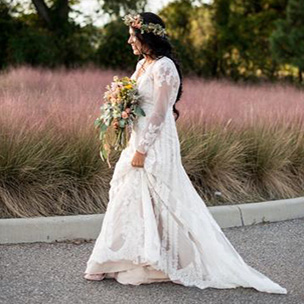 Real bride wearing long sleeve lace Melissa Sweet gown walking outdoors with flowers