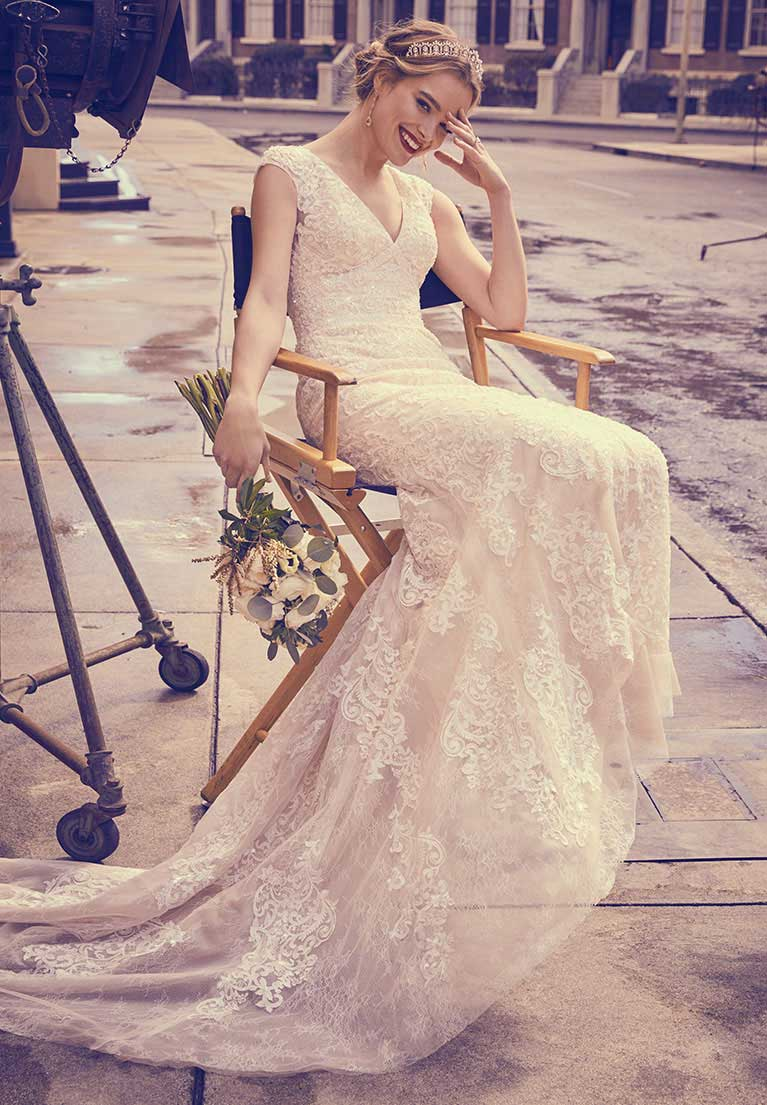 Bride in lace wedding dress sitting in a director's chair on a movie set