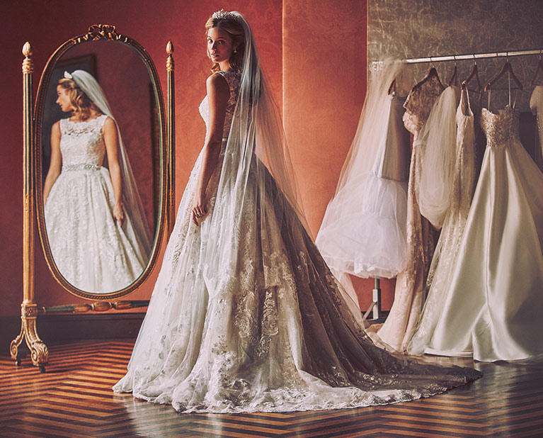 bride in ballgown and long veil looking back from mirror