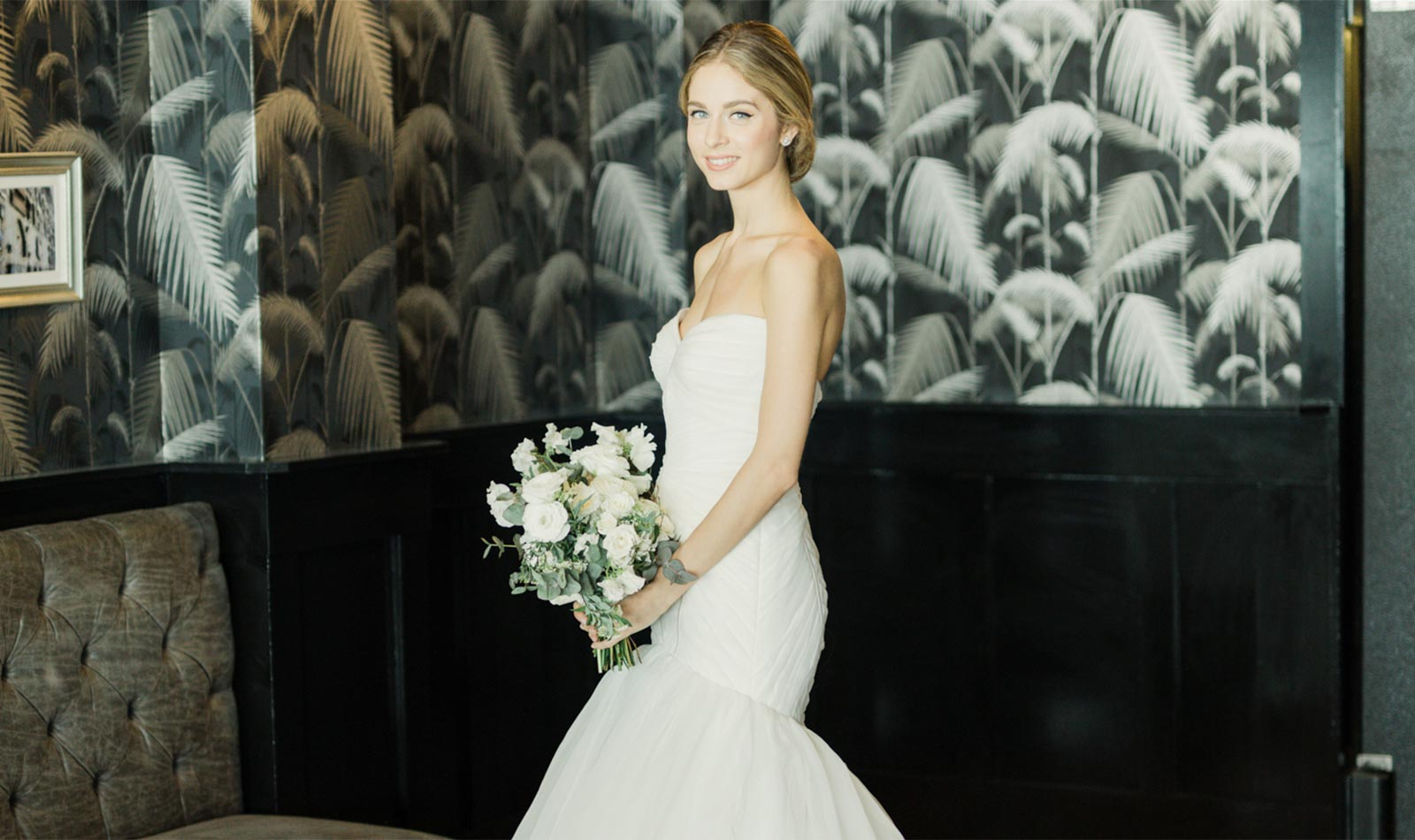 Smiling bride in white Zac Posen wedding gown holder floral bouquet