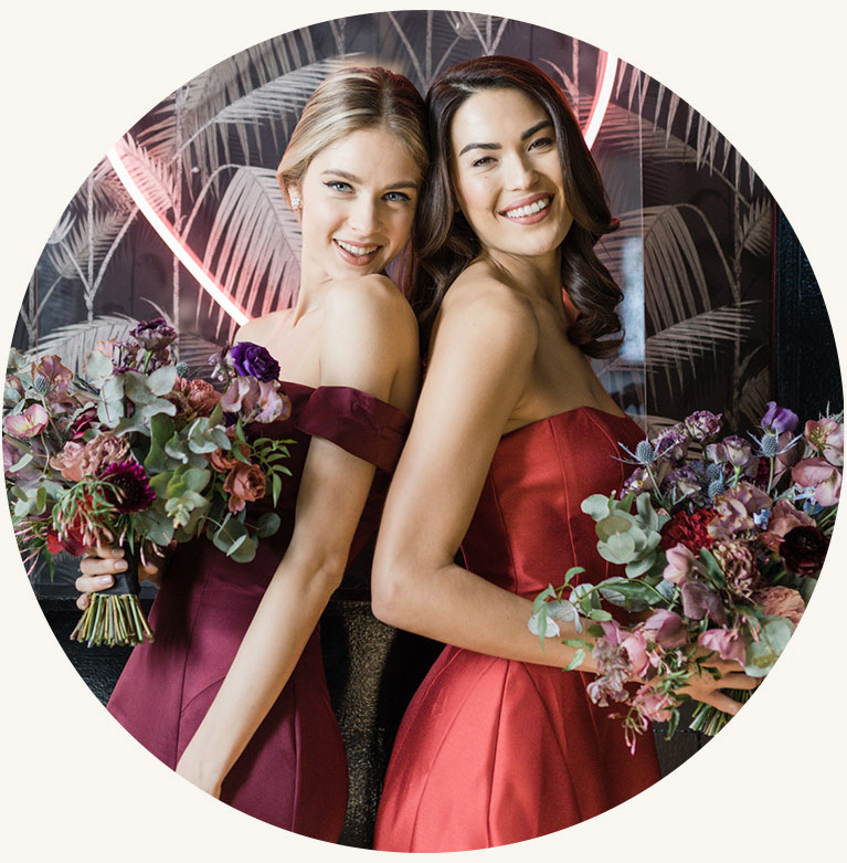 Two bridesmaids in red bridesmaids dresses holder flowers