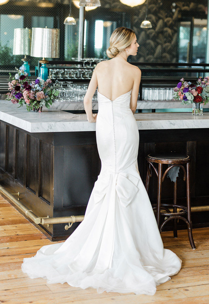 Bride in sleek mermaid bridal gown standing at bar waiting for a drink