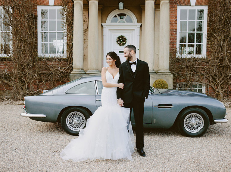 Bride and groom posing outside in front of a classic sports car