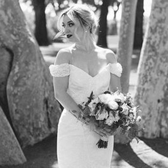 Black and white image of bride with an off the shoulder wedding dress looking off to the side