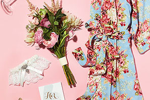 Floral print robe, lingerie and a bouquet laying on a pink background