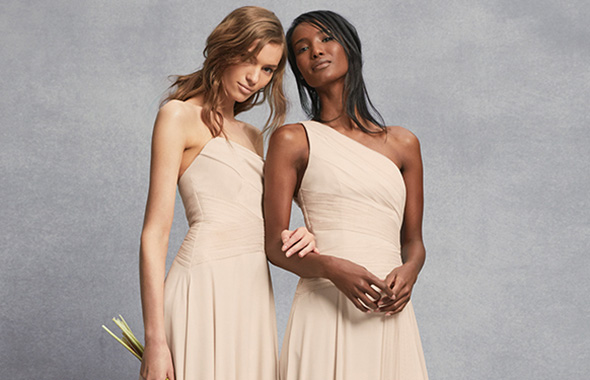 two bridesmaids in cream colored dresses linking arms