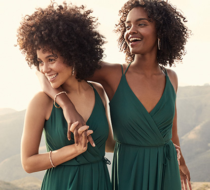 Bridesmaids in dark green dresses with their arms around each other smiling to the side