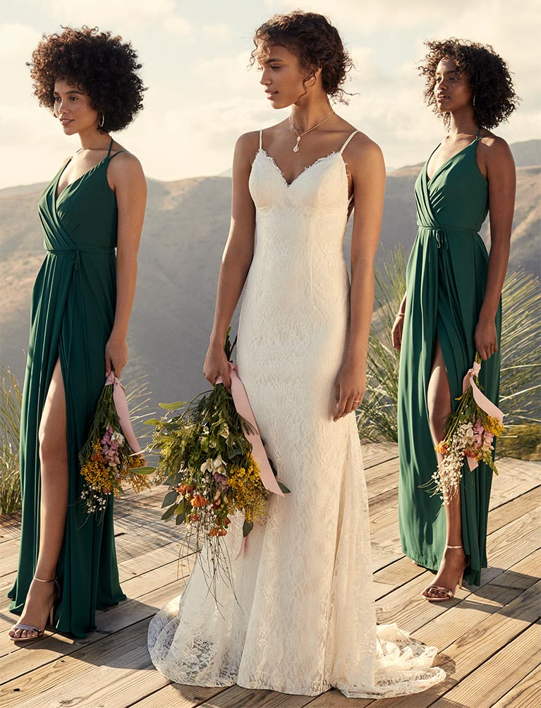 Bride standing on cliff side deck with bridesmaids in green staggered by her