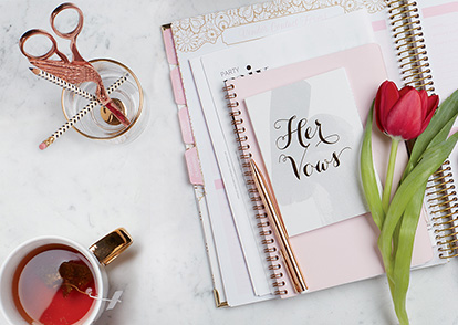 Wedding planner with tulip, vow book, and tea