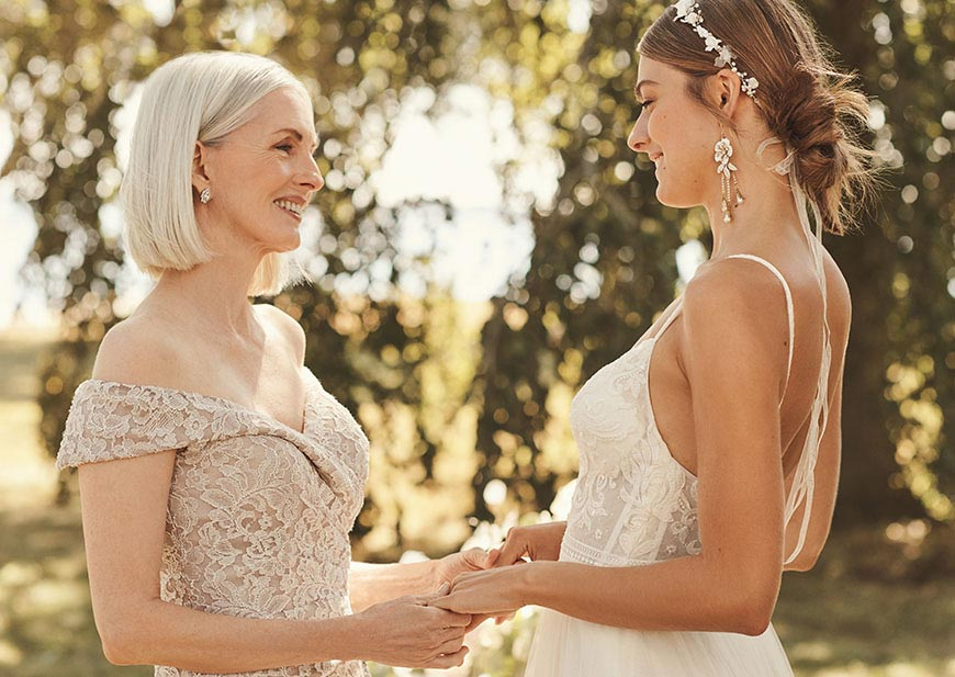 Mother of the bride wearing cream lace off the shoulder dress standing with bride.
