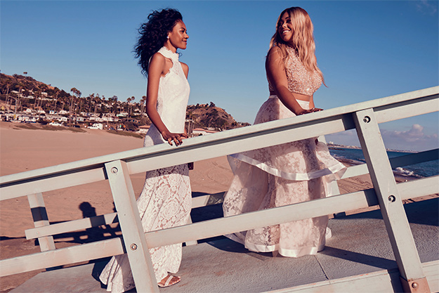 2 girls in embellished lace prom dresses at the beach