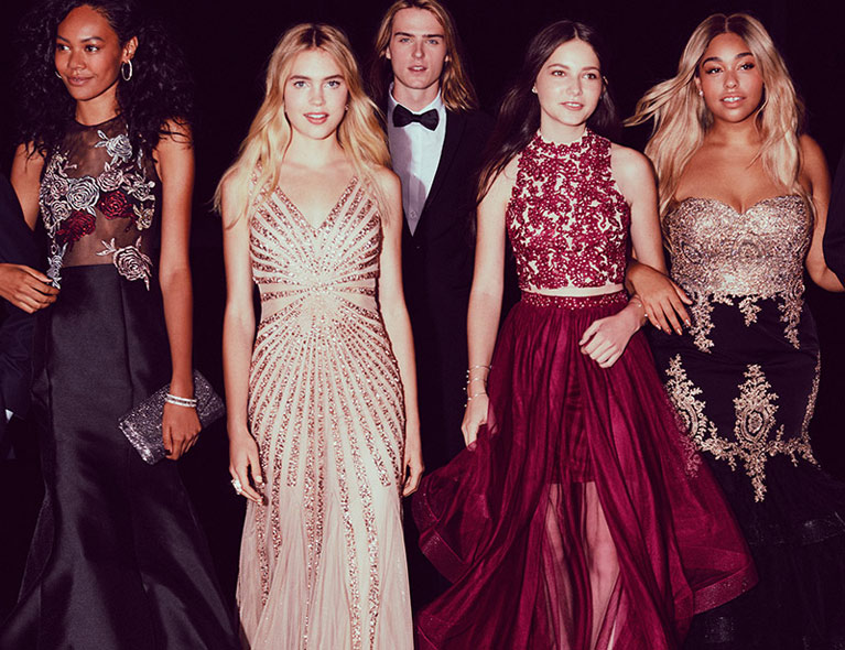Four girls in a variety of prom dresses accompanied by 2 boys in tuxedos