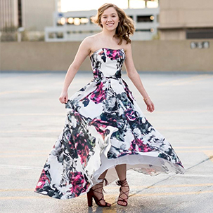Prom girl twirling in printed prom dress on parking garage roof