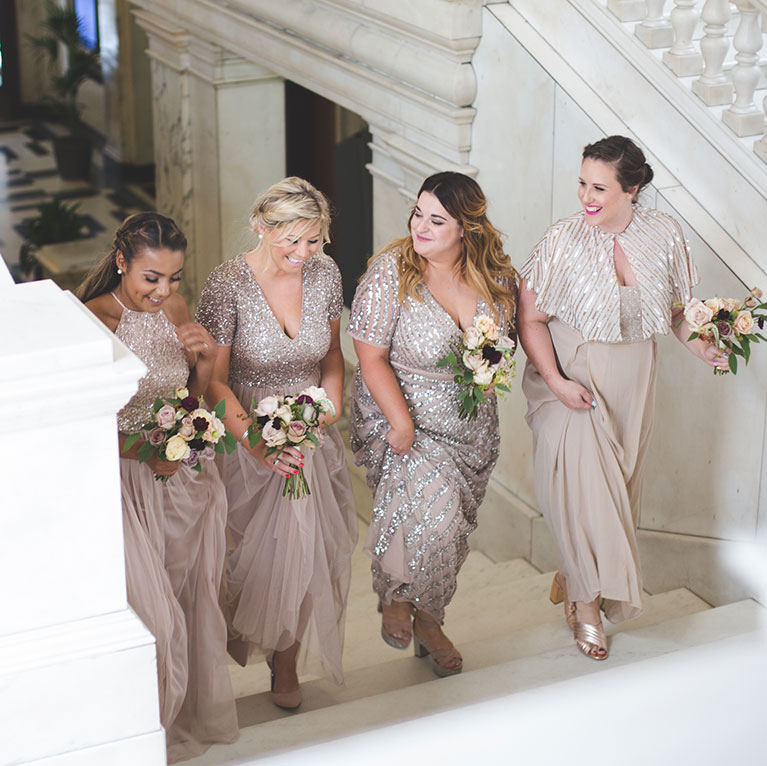 Callie & Dan's Industrial Wedding | Bridesmaid walking with biege dresses