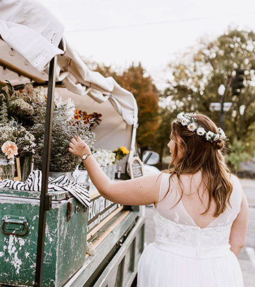Romantic Elopement in Tennessee | Bride Wearing Flower Crown Looking at Flower Cart
