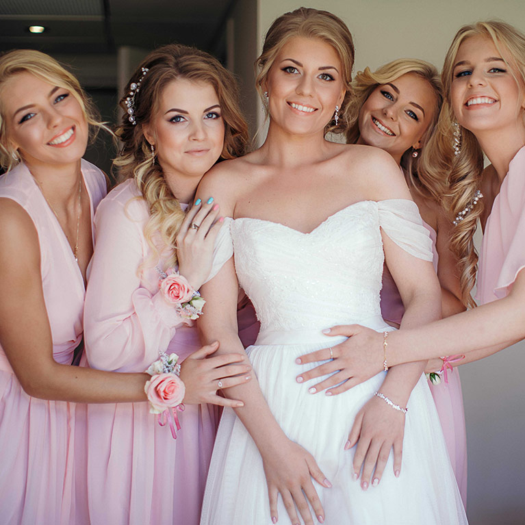 Romantic Beach Wedding | Pink Bridal Party posing with Bride