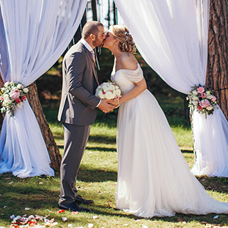 Romantic Beach Wedding | Newlyweds kissing at the arch