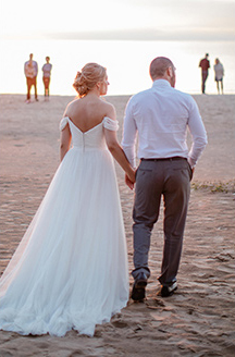 Romantic Beach Wedding | Newlyweds walking into the sunset holding hands
