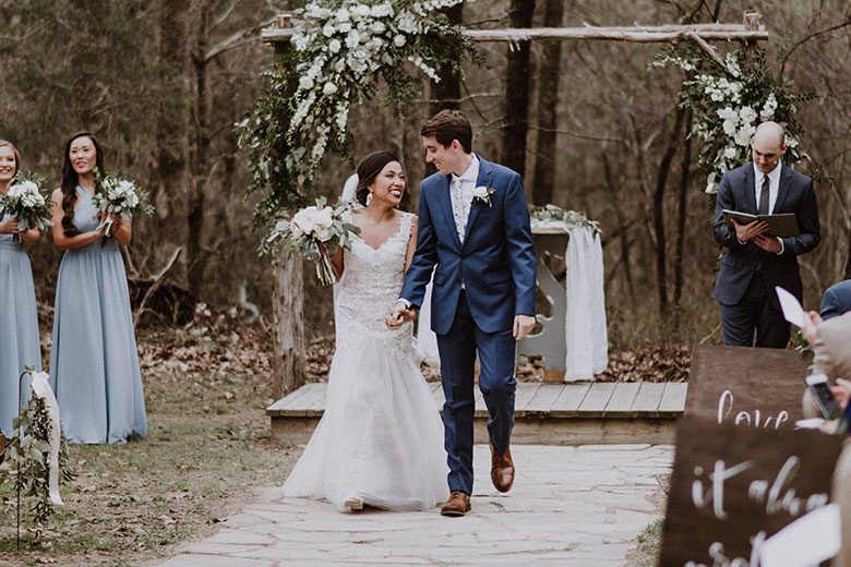 Bride and groom walking down wooded aisle while guests clap