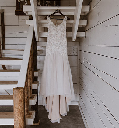 Photograph of dress hanging up on the back of a stairwell