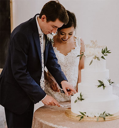 Bride and groom cutting white cake with greenery