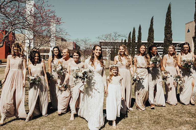 Bride walking surrounded by bridesmaids and bouquets