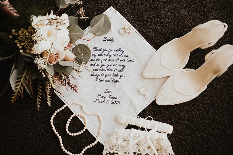 Laydown image of handkerchief, shoes, pearls, bouquet and garter