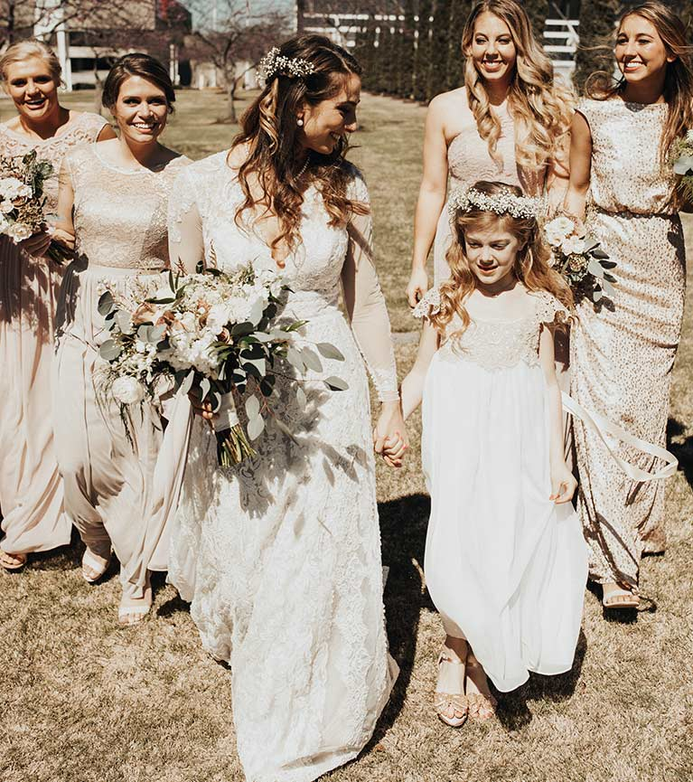 Bride walking and holding flower girl's hand