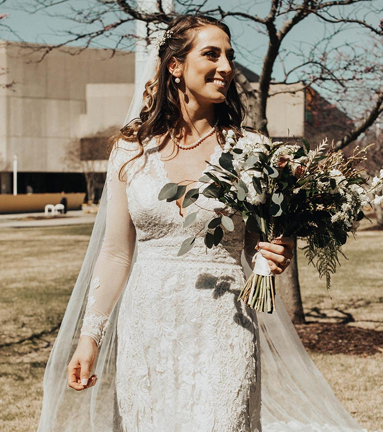 Bride smiling holding bouquet while walking