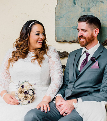 Wife and Husband Sitting on Bench Smiling | David's Bridal