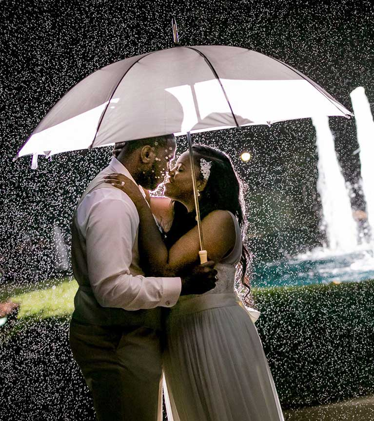 Bride and Groom Kissing Under Umbrella While Raining