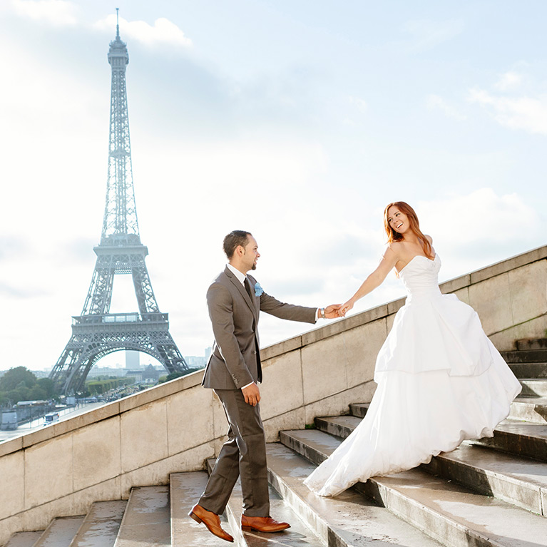 Bride and groom happily holding hands on stairway in front of Eiffel Tower
